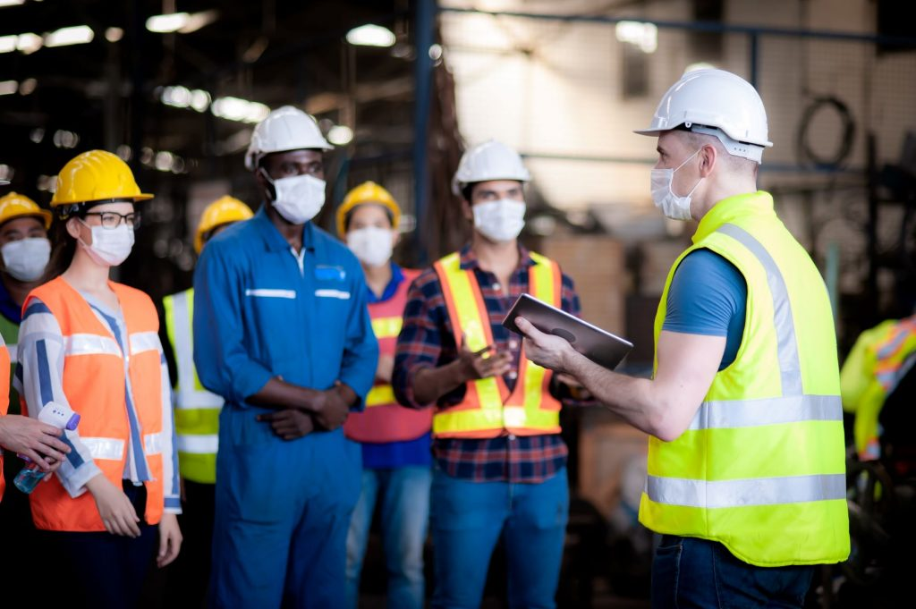 Six people wearing warehouse clothes and PPE standing in a warehouse.