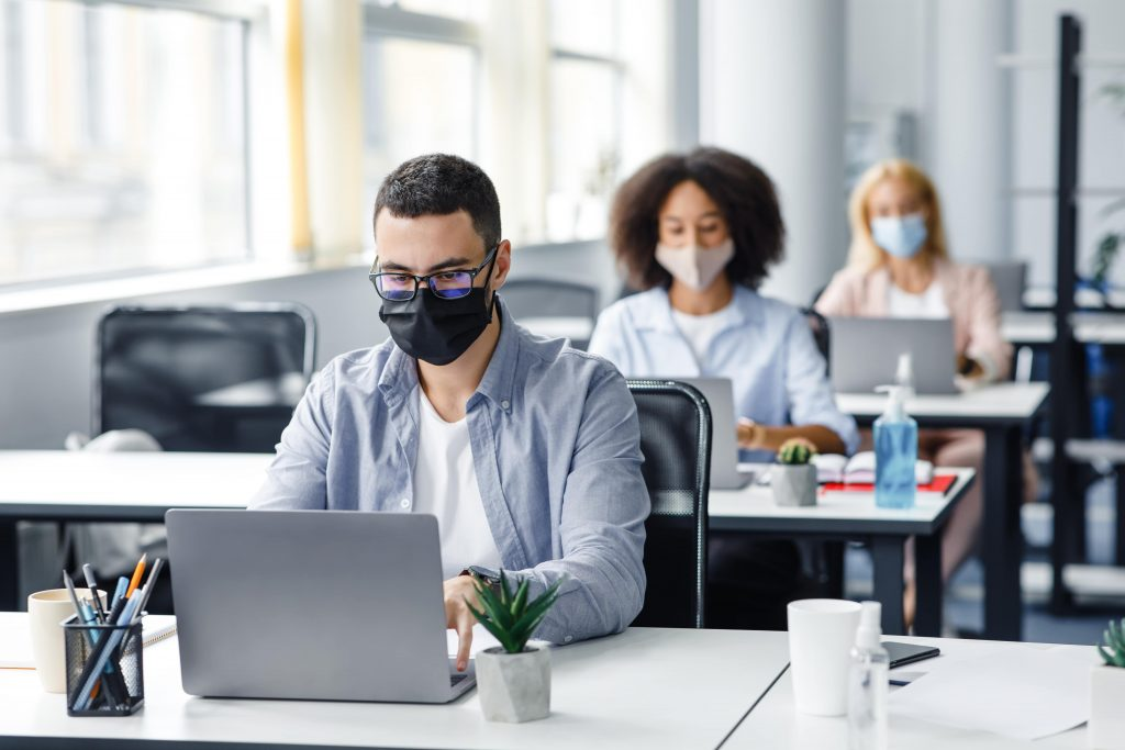 3 people wearing face masks at their desks