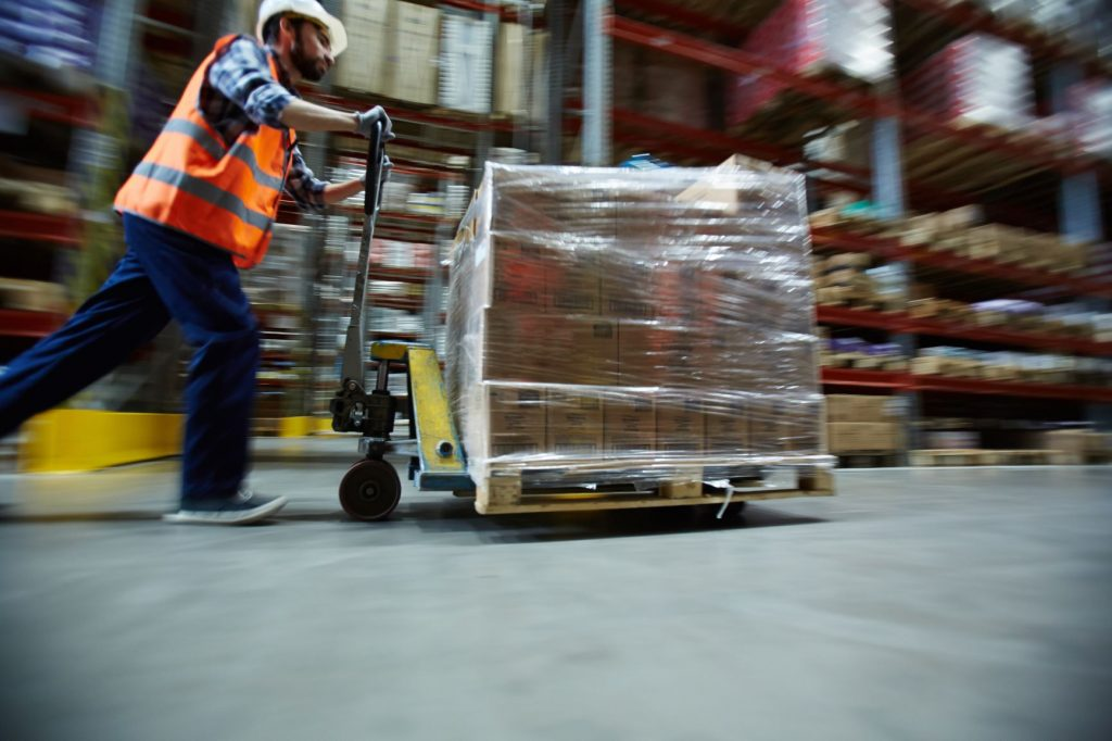 Man wearing reflective vest pushing products on dolly in warehouse